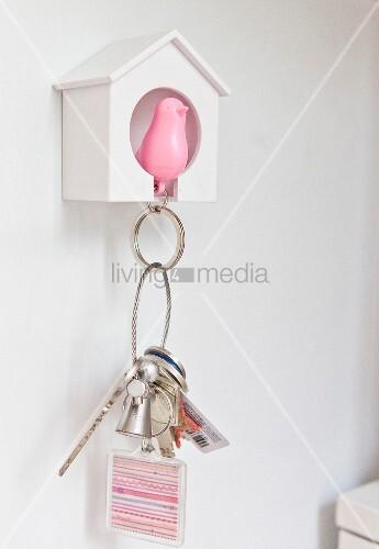 Schlüsselaufbewahrung an weißem Häuschen mit rosafarbener Vogelfigur