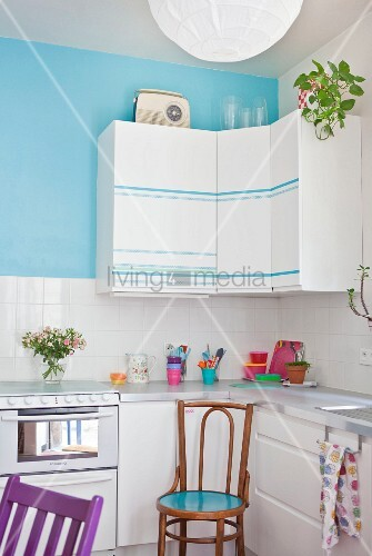 Wall units with striped fronts on turquoise wall in white fitted kitchen
