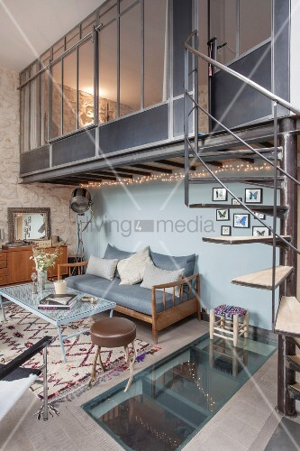 Living space in industrial loft apartment with spiral staircase leading to mezzanine