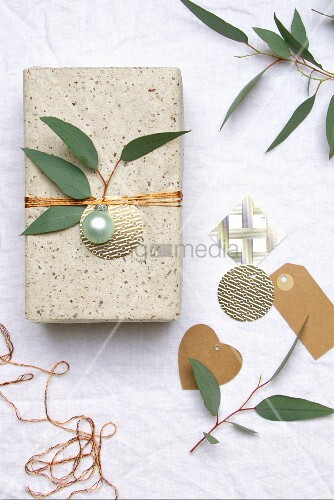 Wrapped gift decorated with Christmas bauble and sprig of leaves