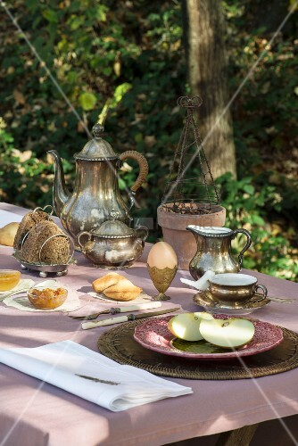 Breakfast table set with silverware, boiled eggs and plate of fruit in garden
