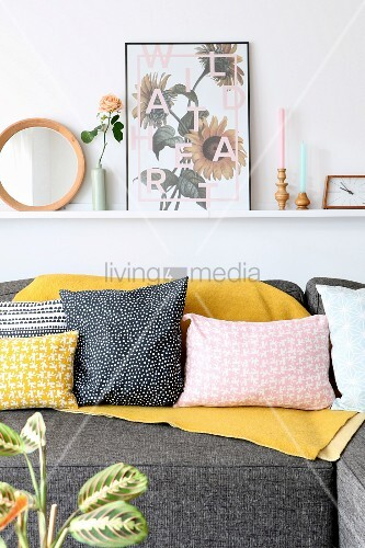 Ornaments on narrow shelf above sofa with various scatter cushions