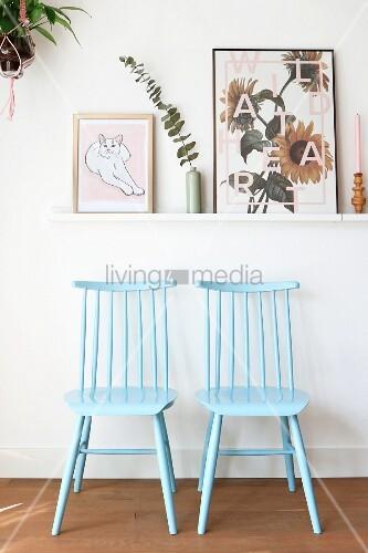 Zwei hellblau gestrichenen Windsorstühle unter einer Bilderleiste