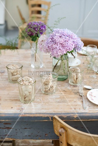 Table set with biscuits in glasses and vases of hydrangeas