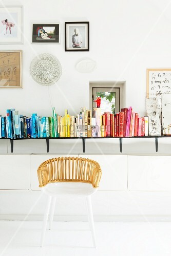 White wicker chair in front of books arranged by colour on wall-mounted shelf