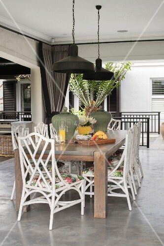 Wooden table and white chairs on veranda with concrete floor