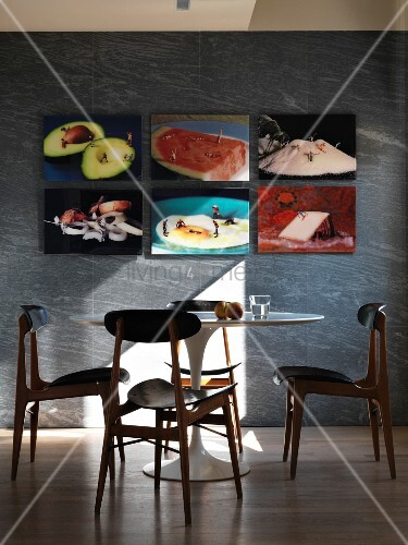 Pictures of culinary motifs above table and retro chairs