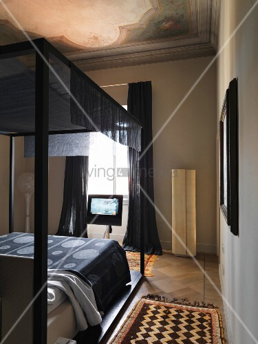 Old ceiling fresco and modern four-poster bed in bedroom