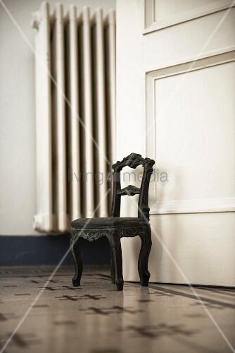 Small metal chair used as doorstop