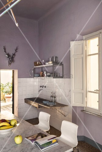 Dining area and old sink on lilac wall in kitchen