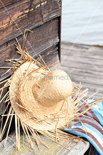 Hand-made straw hat leaning against wooden wall