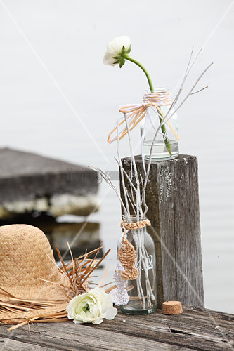 Hand-made straw hat and glass bottle decorated with raffia