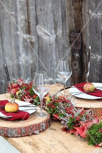 Autumnal place settings on table with rustic wooden boards as place mats and apples on plates