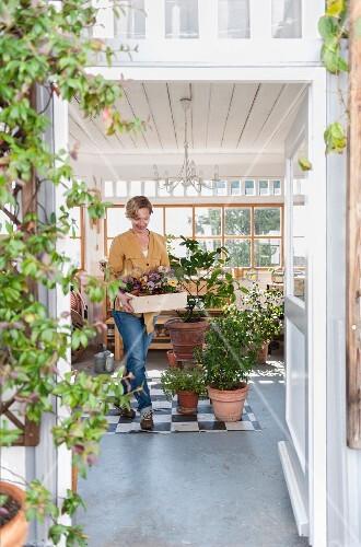 Frau hält Holzkistchen mit Primeln im Wintergarten