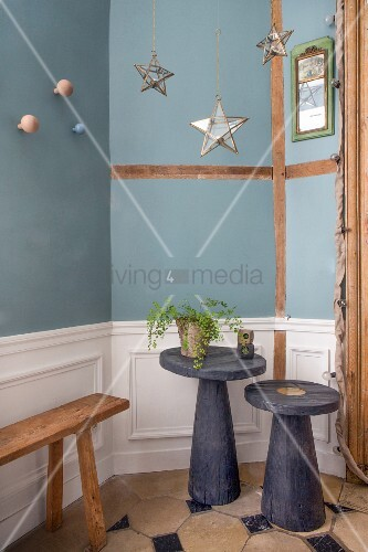 Two side tables in front of blue wall with wainscoting