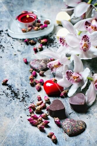 Valentinstag: Pralinen in Herzform zwischen getrockneten Teerosen und Orchideen