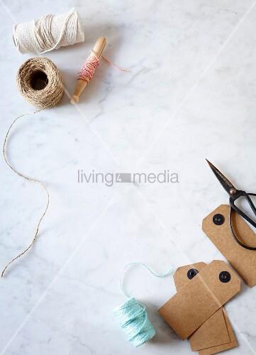Garnrollen und Schnurrolle mit Pappschildern und Schere auf Marmortisch
