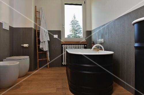 Black, free-standing bathtub against grey wainscoting