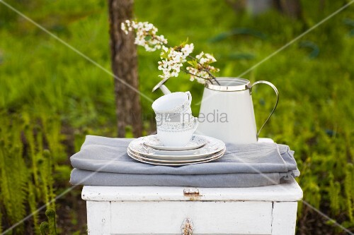 Folded tablecloths, stacked crockery and flowering branches in watering can on white table