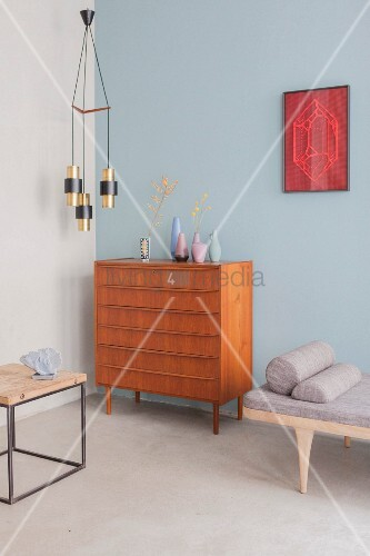 Collection of vases on chest of drawers against pale blue wall below retro pendant lamp