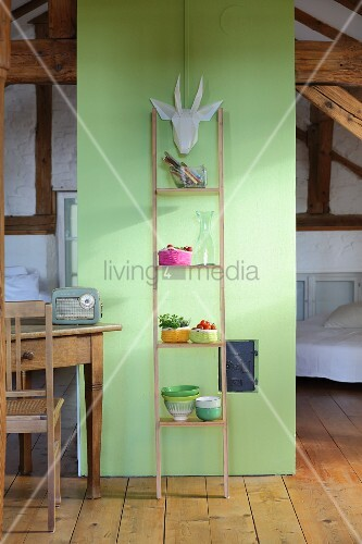 Ladder shelves leaning against green partition in attic room