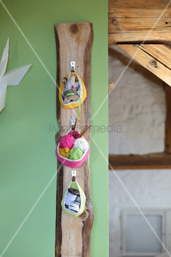 Three crocheted basket hung from hooks on wooden board