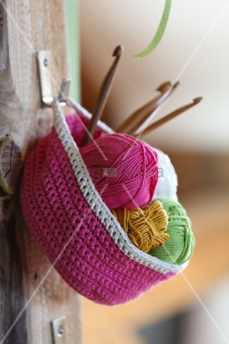 Pink crocheted basket hung from hook on wooden board