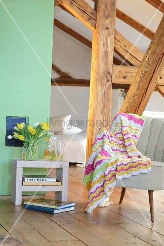 Crocheted blanket with zigzag pattern draped over retro armchair in attic room
