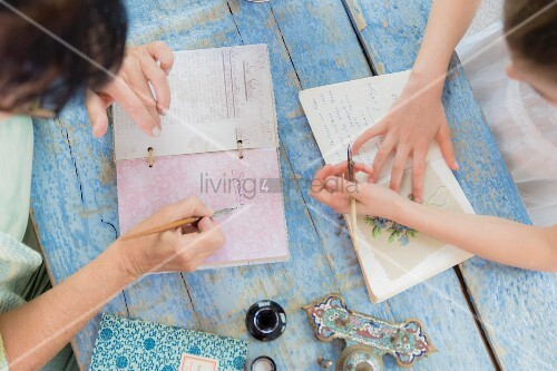 Two people sitting at wooden table and writing in poetry album