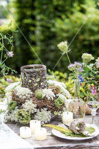 Gedeckter Tisch im Garten mit Wiesenblumen als Deko