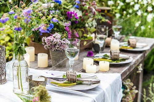 Gedeckter Tisch mit Wiesenblumen und Kerzen im Garten