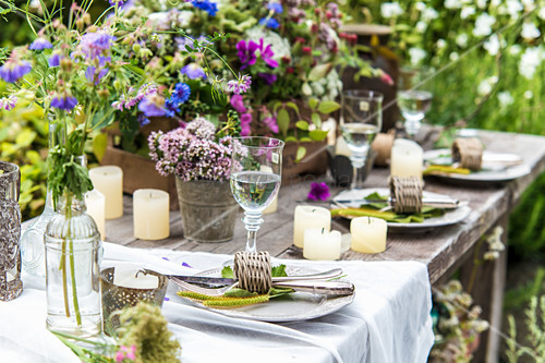 Set table decorated with wildflowers and candles in garden