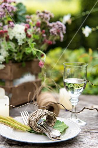 Besteck im Serviettenring aus Korb auf rustikalem Gartentisch
