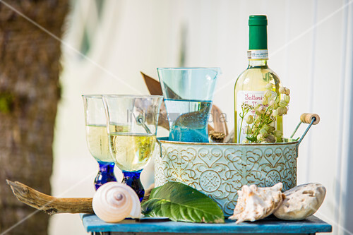 Two glasses next to wine and water in jug in metal basket