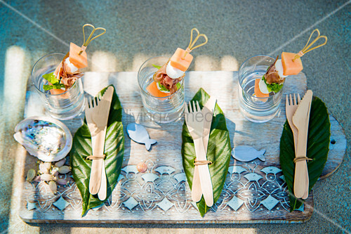 Wooden cutlery on leaves and summery skewers in glasses on tray