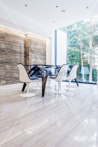 Futuristic dining table on stone floor next to panoramic window