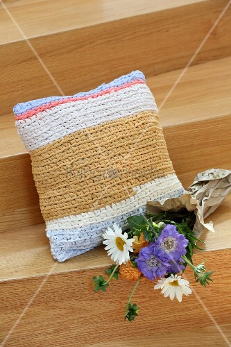 Flowers next to square cushion with crocheted cover made from T-shirt yarn