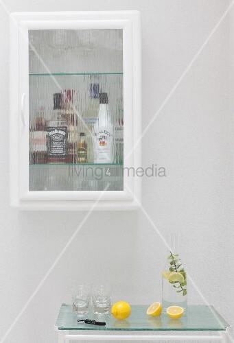 Vitrine mit Getränkeflaschen über einem Servierwagen als Bar