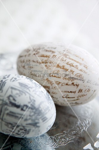 Two eggs printed with lettering and characters on engraved silver plate