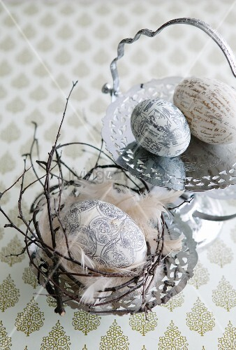 Eggs printed with patterns, lettering and characters in small Easter nest and on engraved silver plates