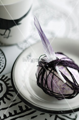 Easter egg painted purple wrapped in cord and decorated with feathers on plate