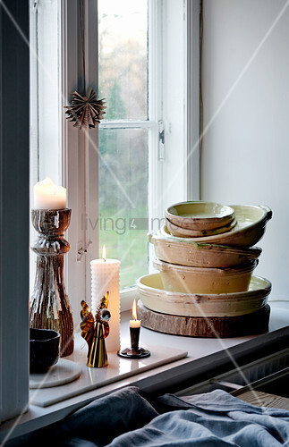 Lit candles and stacked bowls on windowsill