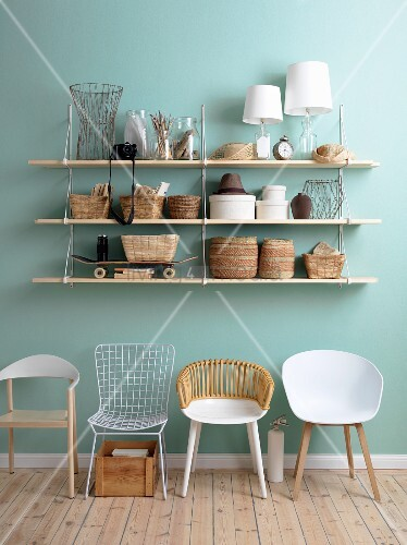 Shelving on blue wall above retro chairs
