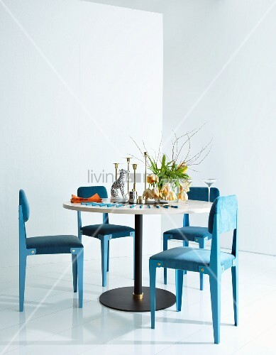 Round table, light blue upholstered chairs, vase of tulips and dog ornament