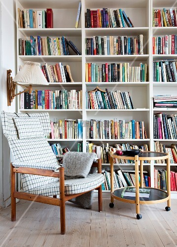 Checked armchair and round side table in front of bookcase