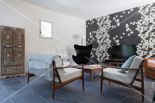 Scandinavian design classics in living room with patterned wallpaper on accent wall