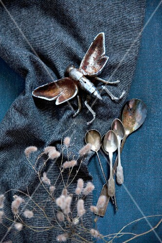 Metal insect figurine and vintage silver spoons on dark fabric