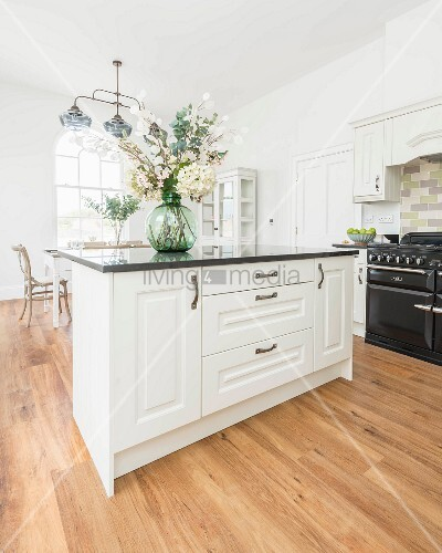 A natural country kitchen with a breakfast bar, granite worktops and a black gas stove