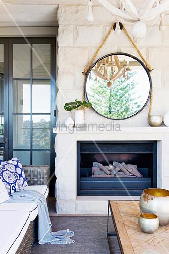 Runder Spiegel hängt mit Tau an Natursteinwand über dem Kamin