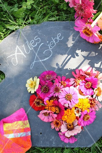 Heart-shaped flower arrangement and chalked message on slate panel